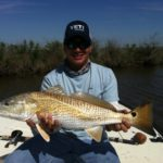 a fisherman with a redfish caught in the backcountry