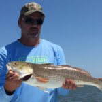 a rockport fisherman with a redfish