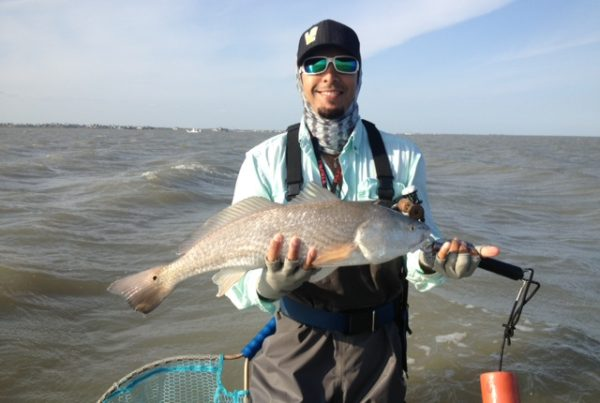 a fisherman with a redfish caught in open water