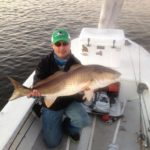 a fisherman showing a big redfish