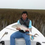 a fly fisherman holding a redfish in the rockport marsh grass