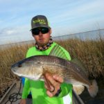 a fisherman showing a marsh grass redfish