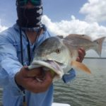a fisherman in rockport texas holding a redfish