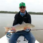 a texas fly fisherman with fresh caught redfish