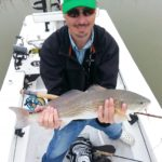 a fly fisherman with a redfish