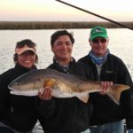 three fishermen showing a large redfish
