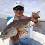 a fisherman holding a rockport redfish