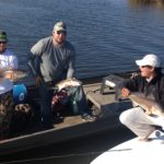 A group of fisherman holding redfish