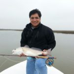 a fly fisherman holding a redfish