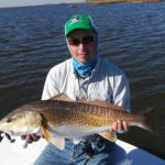 a fisherman showing a large redfish in texas
