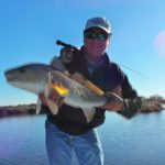 a fly fisherman showing a redfish on a clear day
