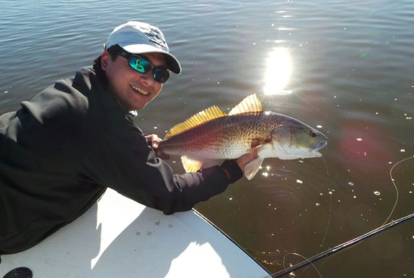a fisherman showing a redfish caught in Rockport