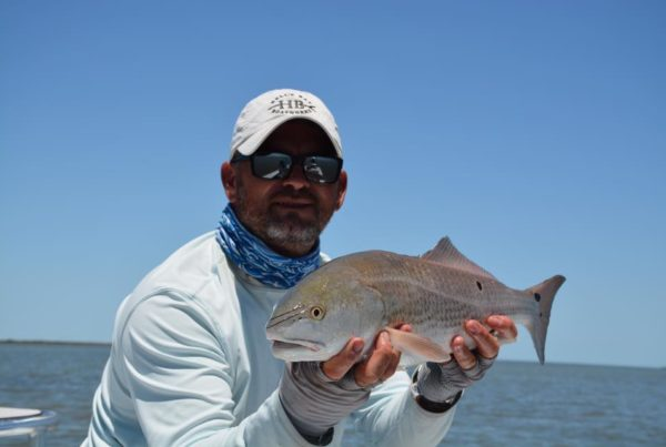 a fisherman holding a redfish caught in rockport